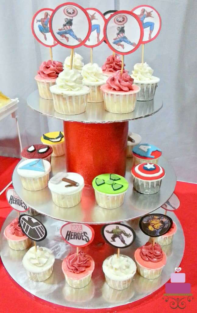 A red and silver cupcake holder with Superheroes themed cupcakes