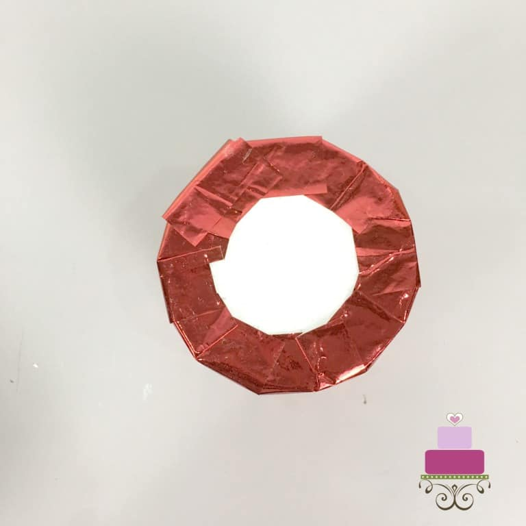 Red paper wrapped around a styrofoam cylinder to form the core of a DIY cupcake holder