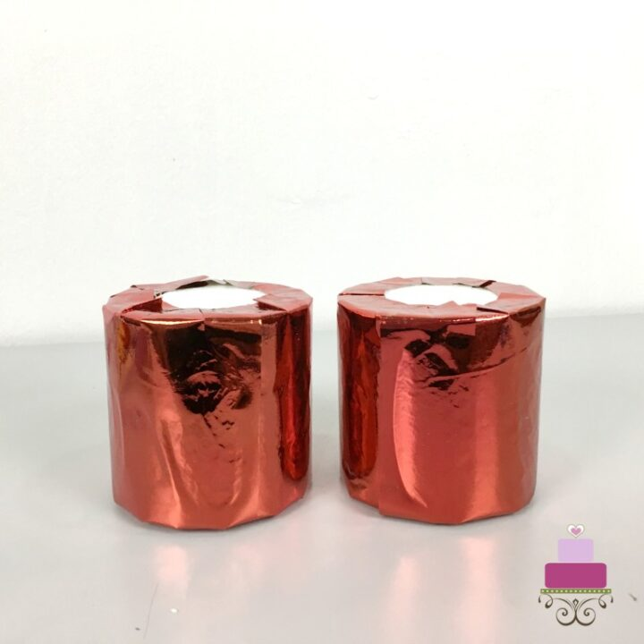 2 styrofoam cylinders wrapped in red shiny paper for a 3 tier cupcake holder
