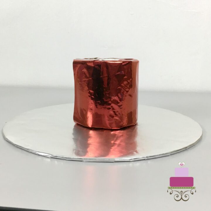 A red cylinder styrofoam block on a piece of round silver cake board.