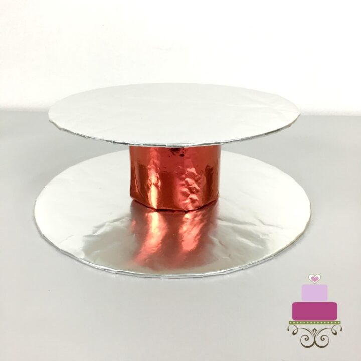 A red cylinder block of styrofoam wrapped in red paper, in between 2 silver cake boards