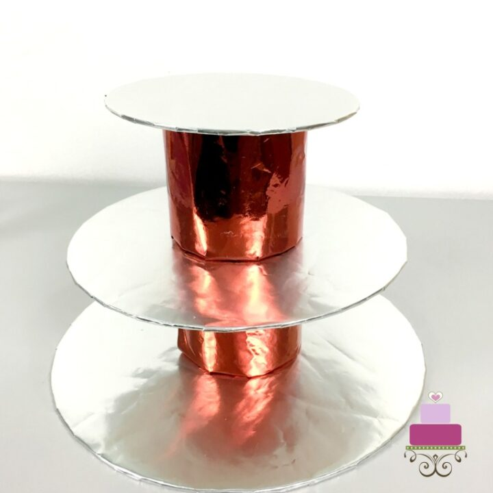 3 silver cake boards with 2 cylinder blocks of red paper wrapped foam blocks in between to form a DIY cupcake holder