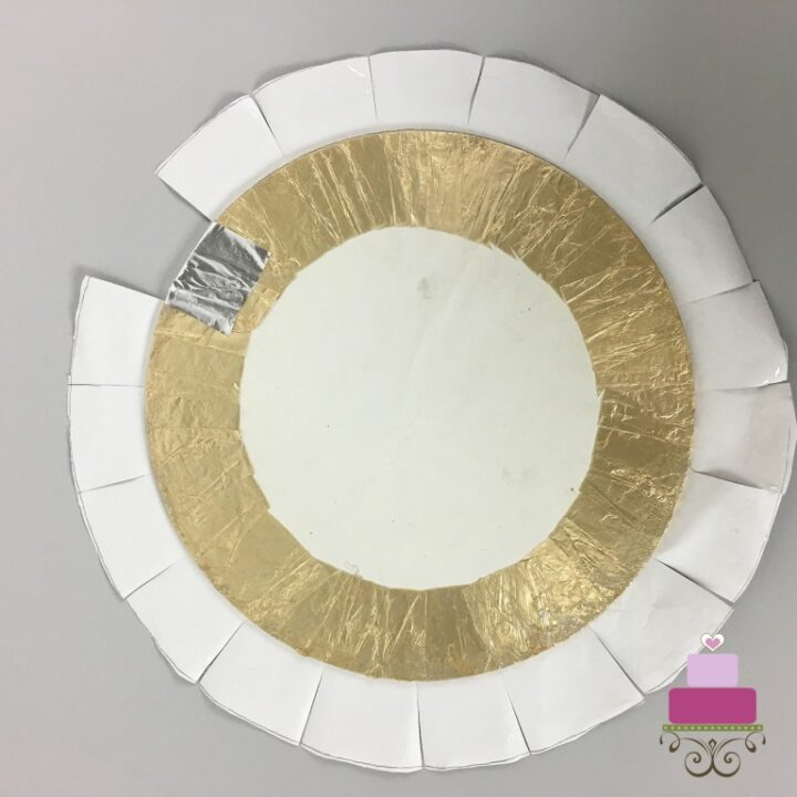 A cake board on a piece of round paper with the edges cut in intervals of about 1 inch