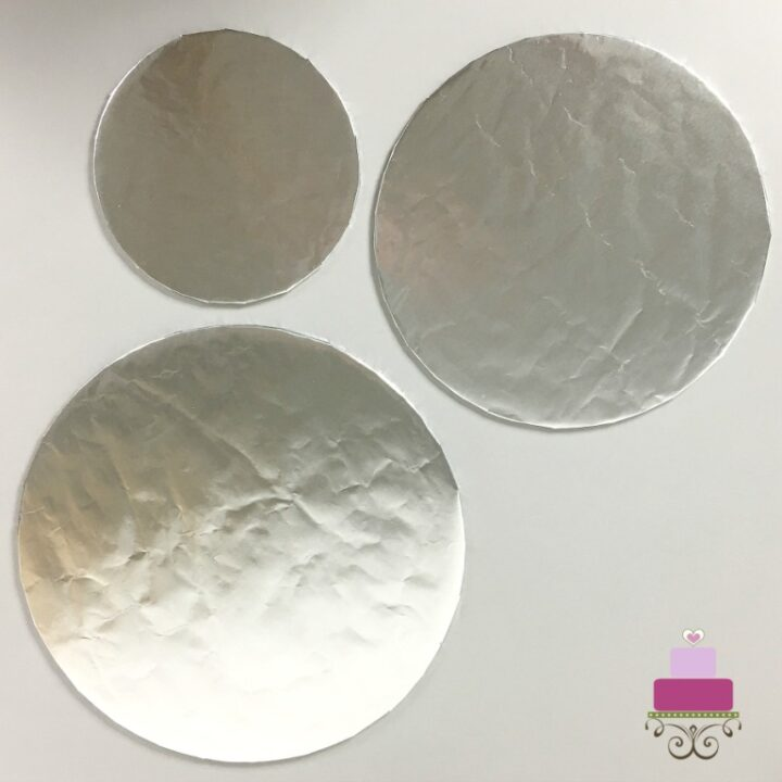 3 cake boards wrapped in silver paper for the DIY cupcake holder