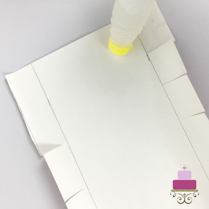 Applying glue to a piece of cut paper