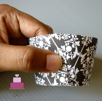 A damask patterned cupcake wrapper held around a cupcake casing