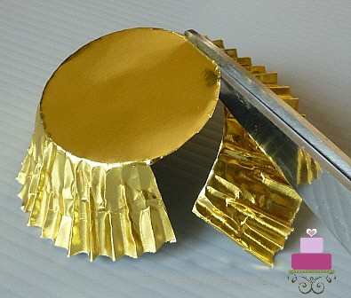 Cutting a gold cupcake casing