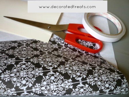 A red pair of scissors, tape and damask patterned paper