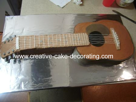 A guitar shaped cake in brown and white