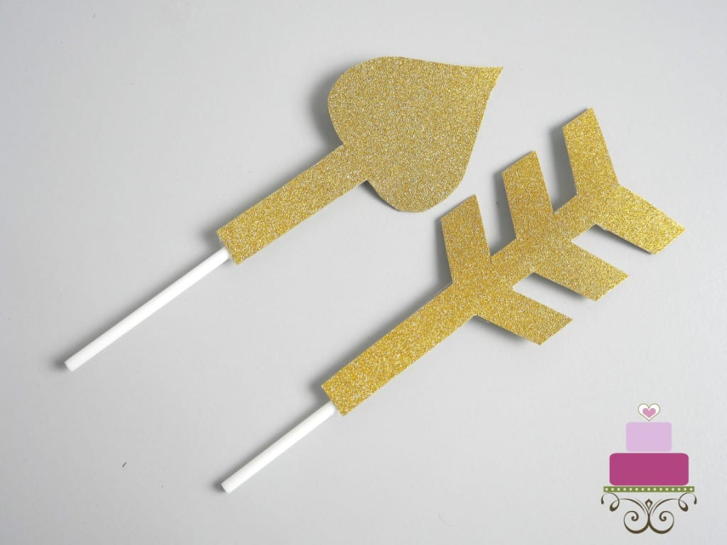Gold paper arrow with white sticks attached