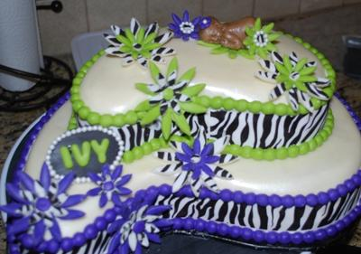 2 tier paisley shaped cake decorated in zebra strips design on the sides and a sleeping baby topper.