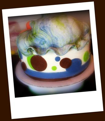 A round cake with a baby bum topper and baby feet.