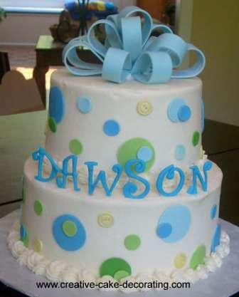 A 2 tier white cake decorated with a blue fondant loop bow and round fondant cut outs in blue and gree.