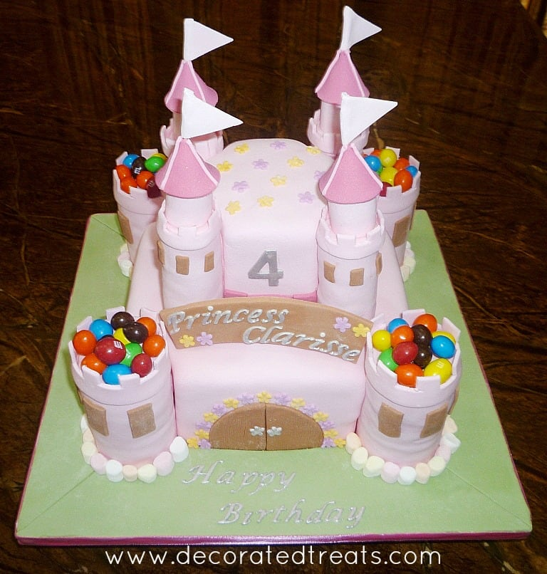 A pink, 2 tier castle cake decorated with colorful candies