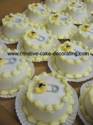 White cupcakes with baby pin design.