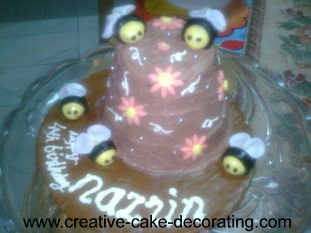 A 2 tier brown cake with fondant bees decoration.