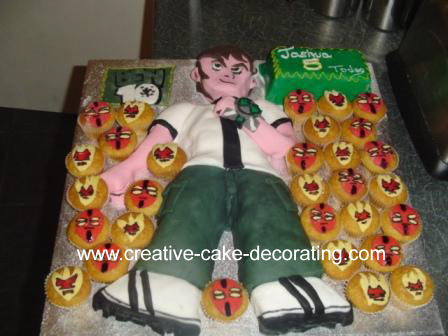 Ben 10 shaped 2D cake with cupcakes on the side