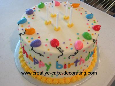 Round white cake with colorful candles icing design