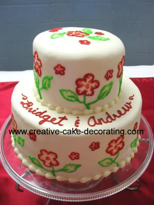2 tier cake with red and green floral brush embroidery design