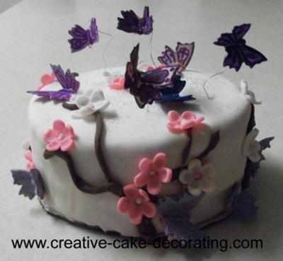 A round cake with 3d butterflies on wires.
