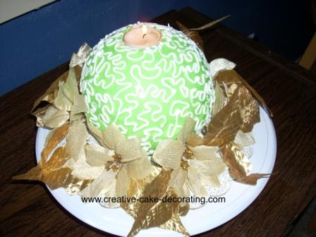 Green round cake with tea candle in the centre