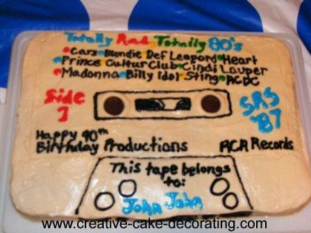 A cassette tape shaped cake in white with black lettering