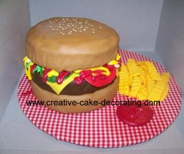 A hamburger shaped cake on a checked cake board.