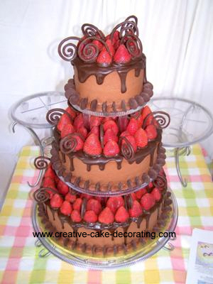 3 tiered chocolate covered cake with strawberries in between each tier and chocolate scroll designs