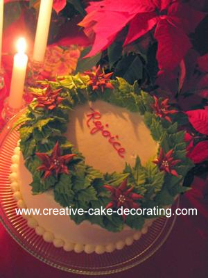 Round white cake with green and red poinsettia wreath design on top