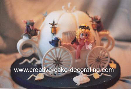 White carriage shaped cake with Cinderella figurine on the side.