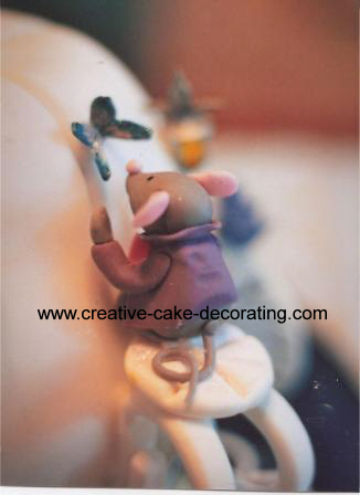 Fondant mouse figurine on the side of a cake