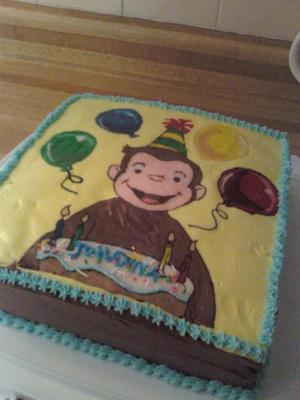 A rectangle cake with Curious George image in party hat.