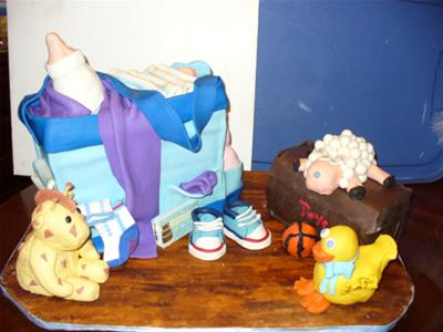 A cake in the shape of a diaber bag, along with 3d fondant baby items.
