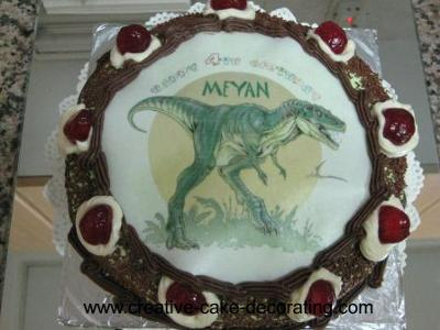 A round cake with a dinasour image in the center.