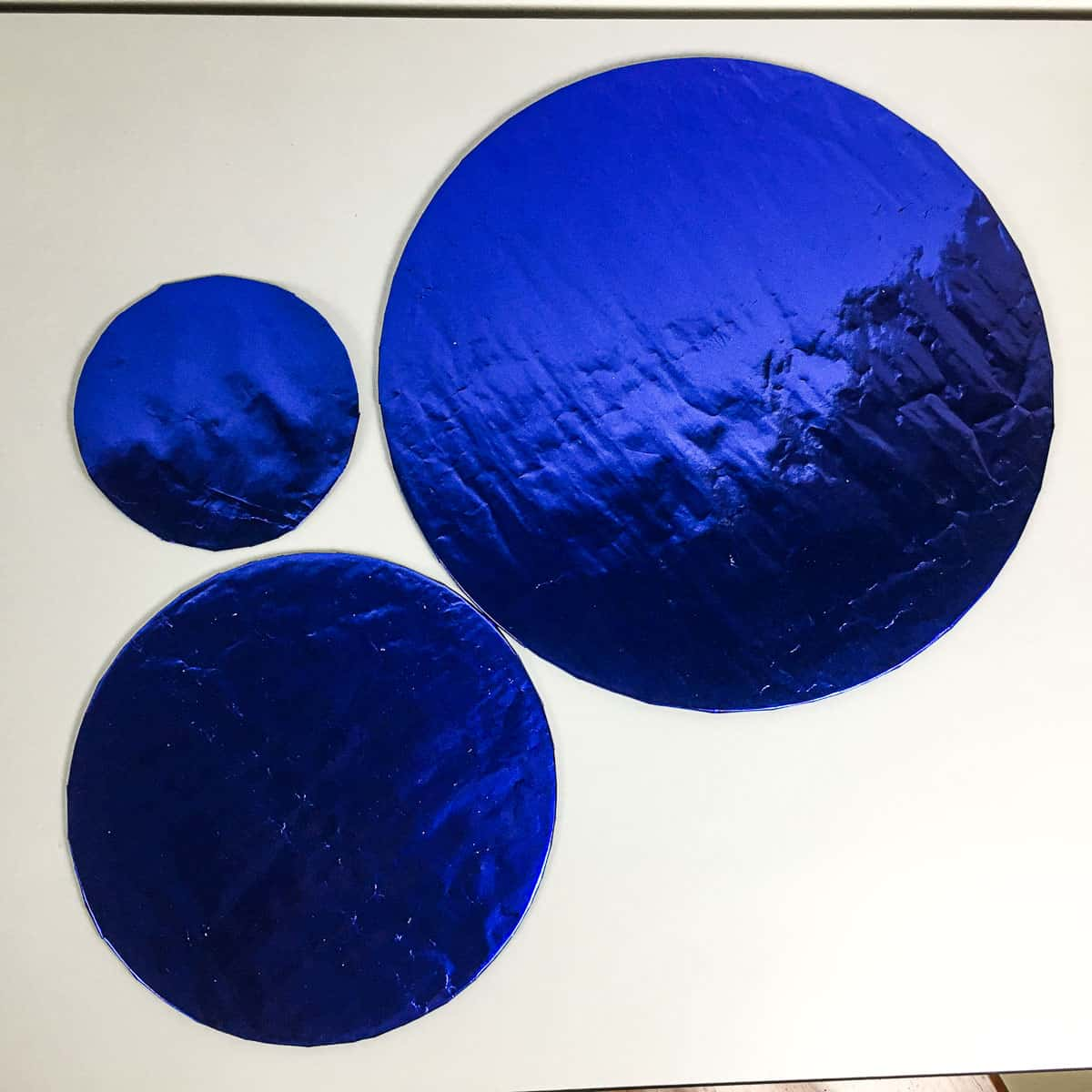 3 pieces of cake boards wrapped in shiny blue wrapper.