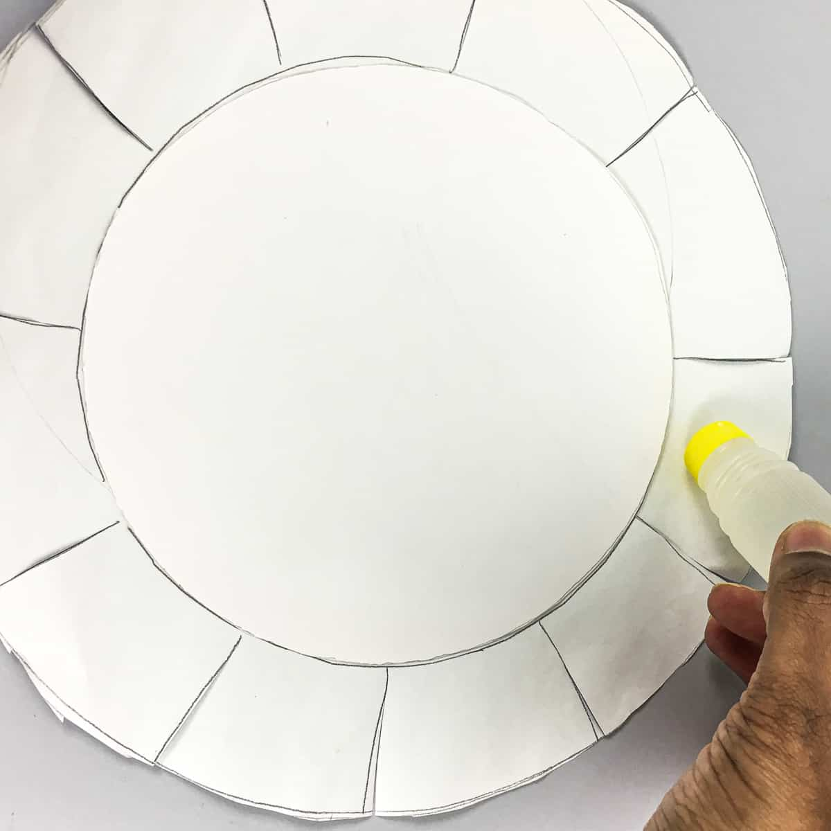 Applying glue to the a piece of round paper