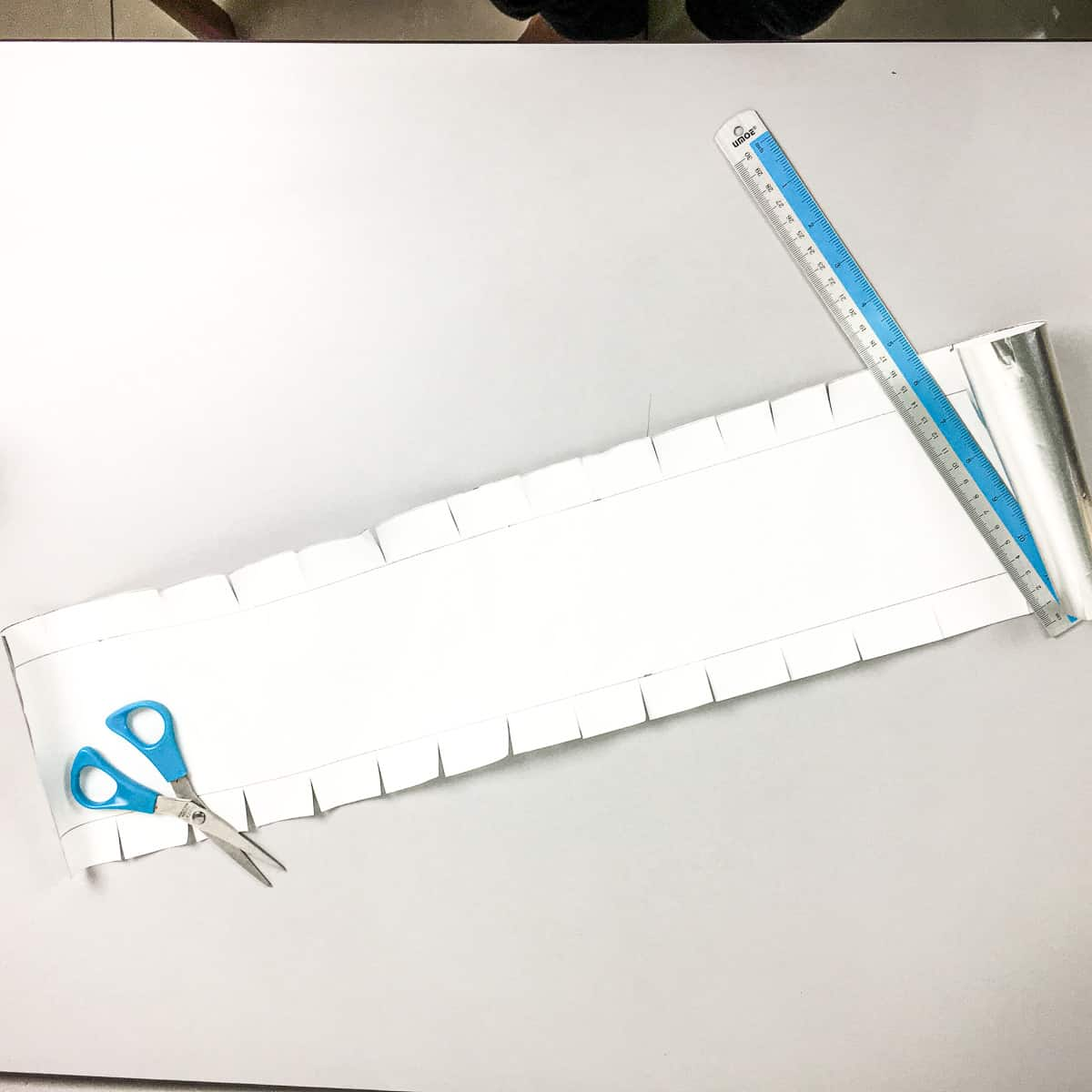 A long piece of paper with the sides snipped being held down with a pair of scissors and ruler