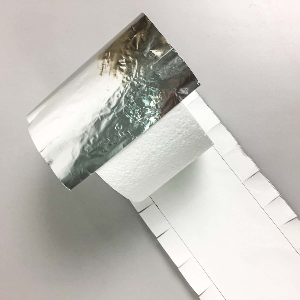 A round styrofoam block being wrapped in silver paper