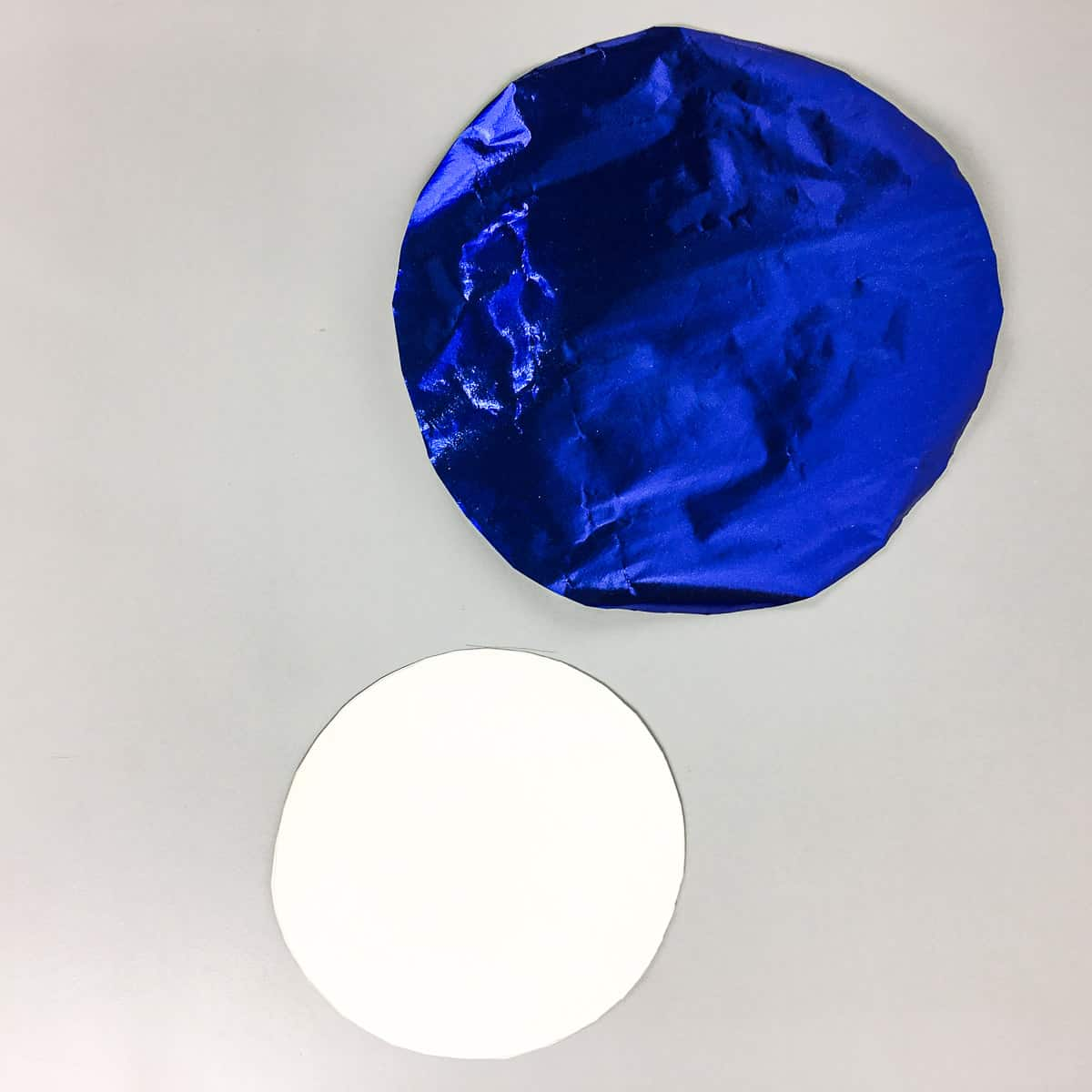 2 cake boards, one wrapped in blue paper and another one in white