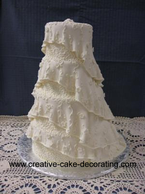A 4 tier cake with white frilly design on each tier.