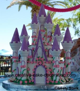 White, 2 tier castle cake with white and purple turrets and floral decoration.