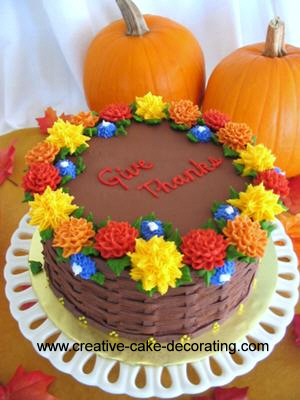Brown round cake with basket weave sides and decorated in red, yellow, orange and blue flowers