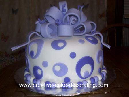 White cake with purple fondant loop bow and circular fondant cut outs design.