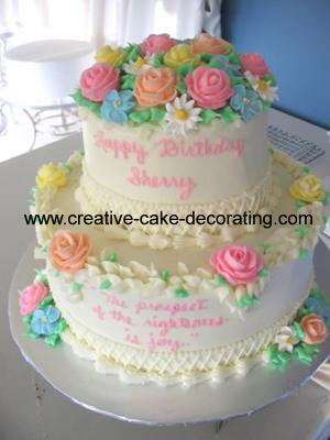 Two tier buttercream cake decorated with pink, orange, blue, yellow and white roses and daisies.
