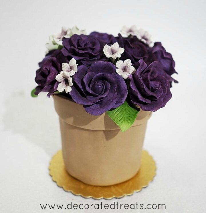 Cake decorating photo of a flower pot shaped cake with light brown fondant pot and purple gumpaste roses. Also included are white filler gumpaste flowers.