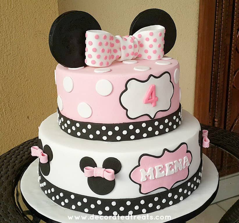 A Minnie Mouse themed cake with fondant bows attached to cake using edible fondant glue