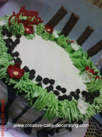 Garden themed cake with icing grass and red flowers.