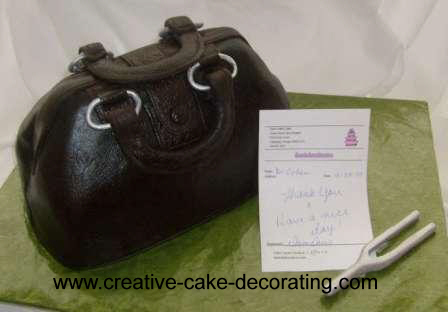 A 3d black handbag cake with a small paper note on the side.