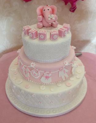 3 tier cake in pink and white, decorated with pink blocks and baby themed deco