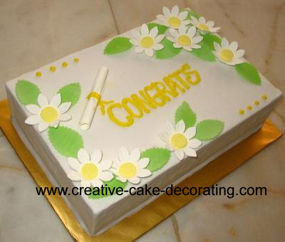White cake with daisies decorated with a small fondant scroll